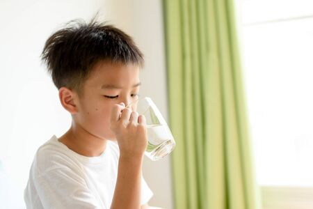 Young boy drink a water from a glass. Banque d'images - 131664824