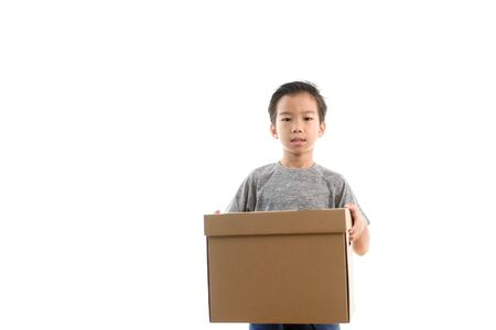 Young Asian Thai boy carry a brown carton box on white background.