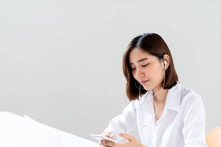 Young Asian woman use a smart phone to listen to music in an office to relax during work Imagens