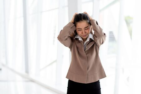 Young Asian unhappy woman looks unhappy and headach in an office. Imagens