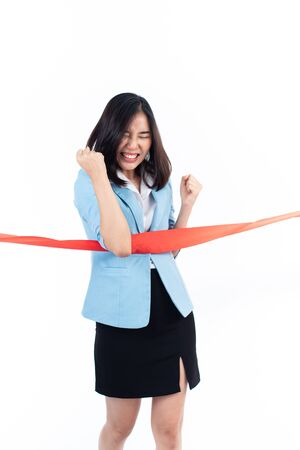 Young Asian Thai woman happy when reach a finish red ribbon line. Competition and success concept. Imagens