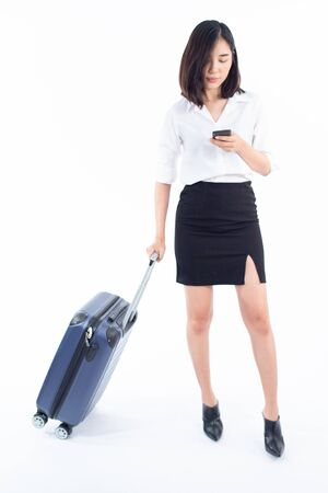 Young business Thai woman use smartphone to check in flight during walking with luggage on white background. Imagens