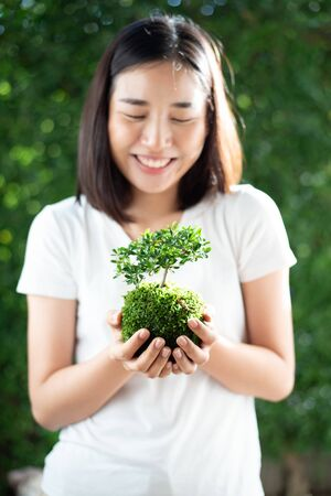Selective focus at young Asian Thai woman carry little seeling plant. Earth day concept. Imagens