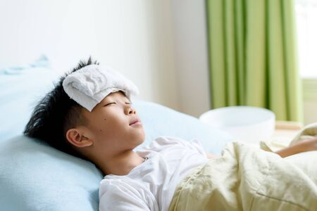 Selective focus at young Asian Thai boy sick and take rest and sleep on a bed in. Banque d'images - 131665940