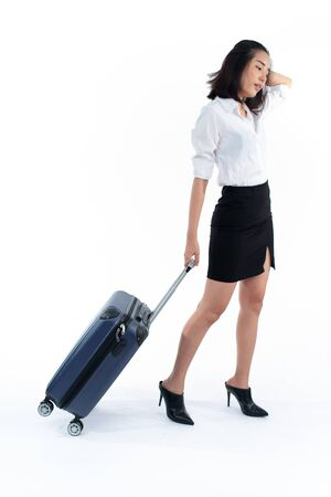 Young business Thai woman walk with a luggage on white background. Business travel concept. 版權商用圖片