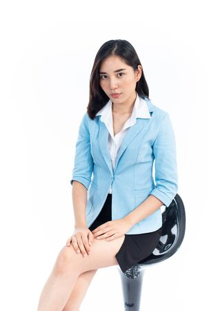 Young Thai woman in business dress sit on a chair on white background. 版權商用圖片