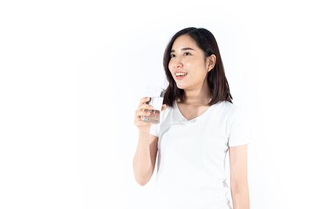 Selective focus at young Thai woman hold a glass of water for drinking on white background.