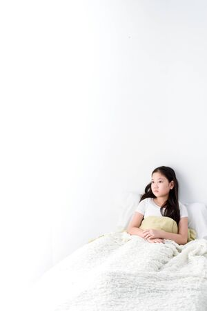 Young Asian girl feel lonely on a white bed. Banque d'images - 131666063