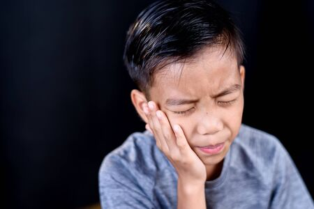 Young Asian boy feel tooth ache and unhappy on black background Banque d'images - 131666390