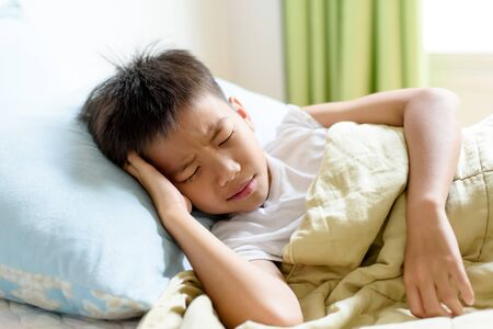 Selective focus at young Asian Thai boy sick and take rest and sleep on a bed in. Banque d'images - 131666457