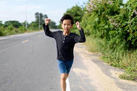 Young Asian boy running on a road in the morning with happiness in summer time. 版權商用圖片