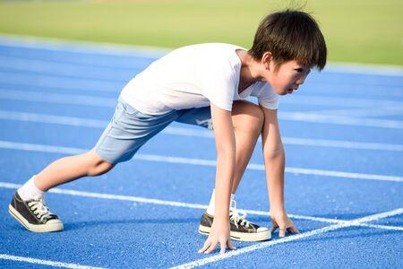 Il giovane ragazzo asiatico si prepara a iniziare a correre su una pista blu in una giornata estiva