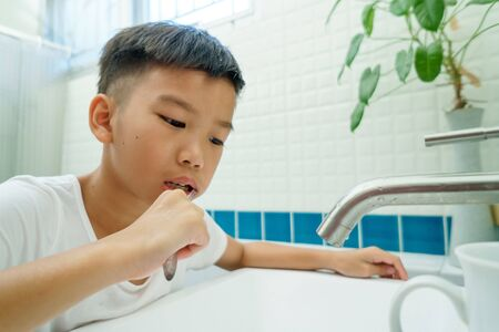 Young Asian boy brush his teeth in a bathroom