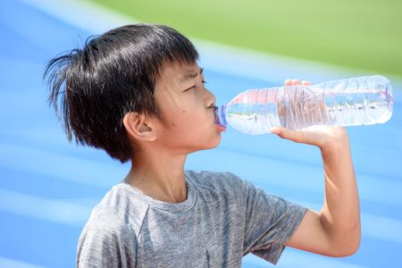 Young Asian boy drink water from a plastic bottle under the sunlight beside a running track to reduce his thirsty. Standard-Bild