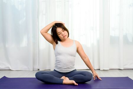 Young Asian woman do yoga in a bedroom during morning. Standard-Bild