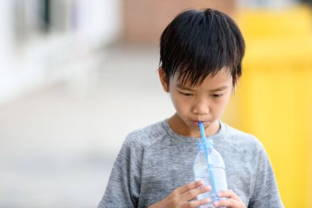 Young Asian boy drink water from plastic bottle by a stra. Stock Photo