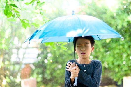Young boy with blue umbrella get cough and feel not good under the rain in a garden.