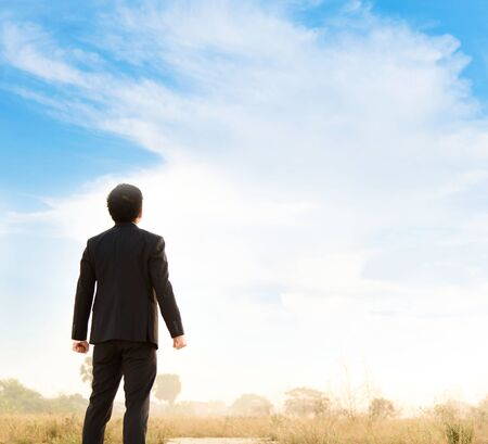 Business man standing looking to the sky. Stock Photo