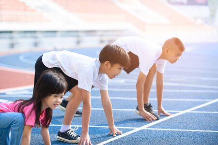 Selective focus at young Asian boy with girl prepare to start running on a blue track Imagens