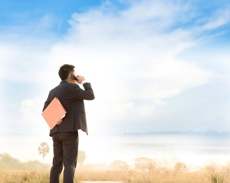 Business man standing and using cell phone on the mountain under blue sky white cloud. Stock Photo