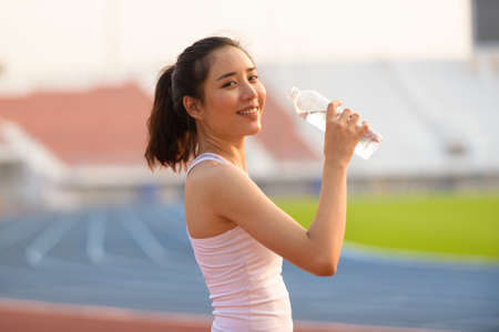 Close up young Asian woman drink water from a plastic bottle after do sport in the morning. Standard-Bild