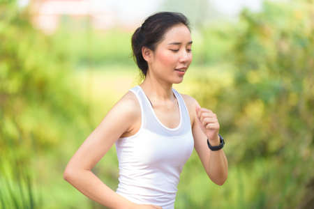 Selective focus at young Asian woman running with happy in a park during summer day in a morning.