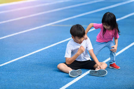 Young boy and girl play on a bluetrack after running in summer