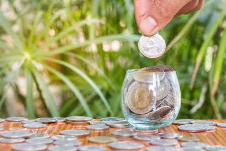 Hand of women putting coin In glass jar , Concept finance business investment