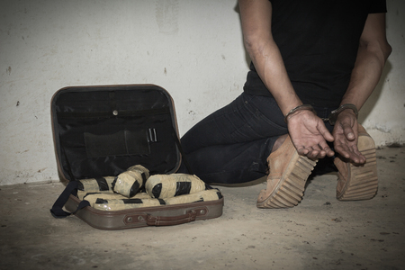 Drug traffickers were arrested along with their heroin. Police arrest drug trafficker with handcuffs. Law and police concept. Stock Photo