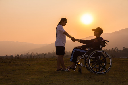 Happy boy in wheelchair with friends Evening sunset.Concept happy child disabled