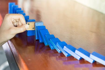 Stop domino risk effect ,businesswomen using hand for management solution. Foto de archivo