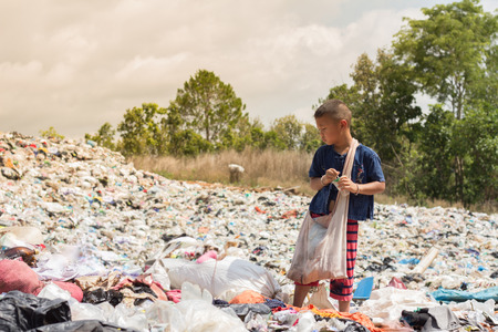 A child find junk for sale and recycle them in landfills, the lives and lifestyles of the poor people. The concept of child labor and trafficking