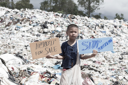 Standing child holding a sign, anti-trafficking, stopping violent acts against children, stopping child labor. Imagens