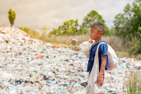 A boy carrying a garbage bag to sell, the lives and lifestyles of the poor. The concept of child labor and trafficking