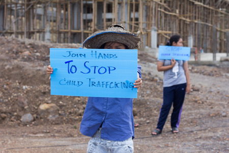 Standing childs holding a sign, anti-trafficking, stopping violent acts against children, stopping child labor.