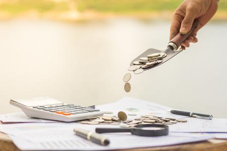 Eine männliche Hand, die eine Kugel Münzen auf einen Stapel legt, spart Geldkonzept,