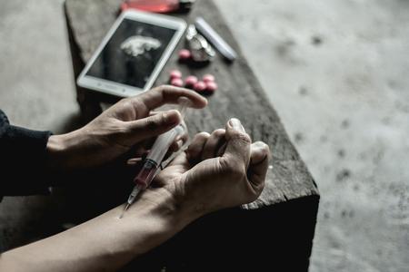 Mädchen injizieren Heroininjektion in Blutgefäße. Das Konzept der Kriminalität und der Drogenabhängigkeit. 26. Juni, Internationaler Tag gegen Drogenmissbrauch und illegalen Handel