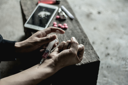 Meisje injecteert heroïne-injectie in bloedvaten. Het concept van misdaad en drugsverslaving. 26 juni, internationale dag tegen drugsmisbruik en illegale handel