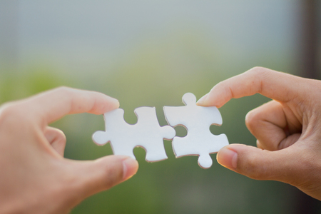 Two human hands connected jigsaw puzzle white, Joint Business Concepts.