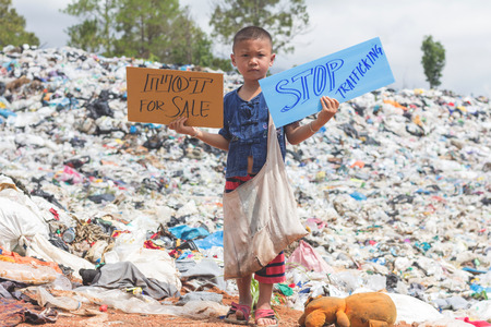 Standing child holding a sign, anti-trafficking, stopping violent acts against children, stopping child labor. Stock Photo