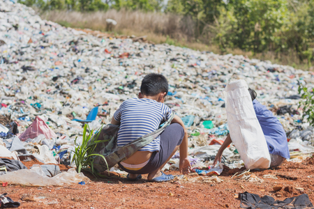 Two children find junk for sale and recycle them in landfills, the lives and lifestyles of the poor, The concept poverty, child labor and human trafficking. Stock Photo