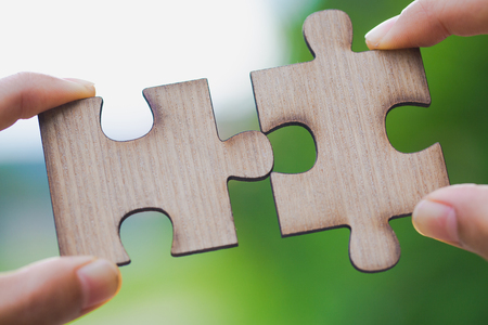 Two hands trying to connect couple puzzle piece with green background.  symbol of association and connection. business strategy.