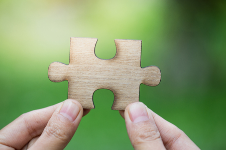 Human hand holding a wooden jigsaw puzzle with green background..  symbol of association and connection. business strategy. Stock Photo
