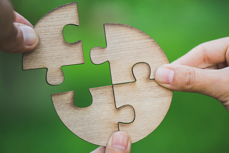 Hand placing the last jigsaw puzzle piece,conceptual of problem solving, Business solutions, target, successful, goals and strategy concepts 版權商用圖片
