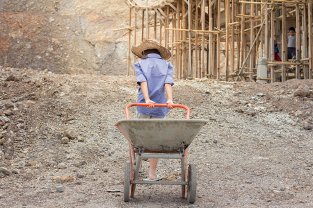 Poor children working at construction site against children labour,  World Day Against Child Labour  and trafficking concept. Standard-Bild