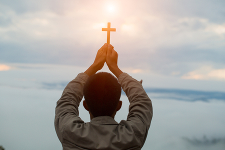 Silhouette off hands holding wooden cross  on sunrise background, Crucifix, Symbol of Faith.