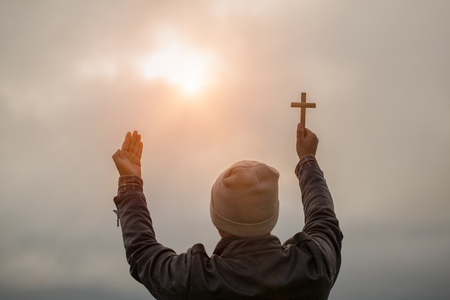 Human hand holds cross and open palm up worship. Eucharist Therapy Bless God Helping Repent Catholic Easter Lent Mind Pray. Christian concept background.