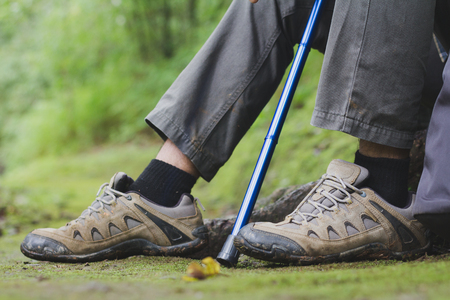 Adventure man hiking with backpack, hiking shoes in action on a mountain  trail path Close-up of male hikers shoes. 版權商用圖片