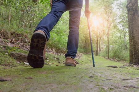 Primo piano delle scarpe di escursionisti uomo. Un uomo cammina lungo un sentiero nel bosco, cammina nella foresta per scalare la montagna.