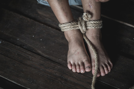 Stop violence Against Children, foot tied up with rope in emotional stress, The concept of stopping violence against children. Human rights Day concept. Anti-trafficking concept. Foto de archivo